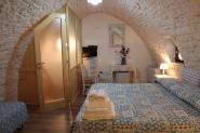 350trulli-donna-isabella-camera-il-noce-letto-matrimoniale-ingresso-bagno